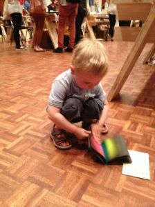 kid with rainbow zine on floor